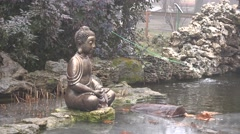Buddhist sculpture stands in the rain next to small pool Stock Footage