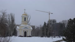 Bell tower of church with Christian cross on background of construction crane Stock Footage