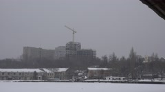 Construction crane and unfinished house on the skyline in the fog, 4k Stock Footage