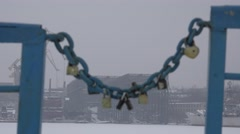 Closed lock on a metal chain on the bridge - symbol of love, shipbuilding cranes - stock footage