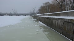 Frozen river in snow, water near granite promenade, pedestrian bridge and harbo Stock Footage