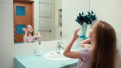 Girl preening. Child 7 years old standing in a bathroom Stock Footage