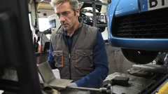 Mechanic working in car repair workshop Stock Footage