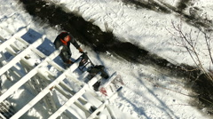 Man using snow plower on the pavement to remove snow  Stock Footage
