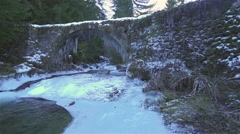 Frozen river in the forest with ancient stone bridge in slow motion Stock Footage