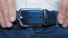 Man's hand tighten trendy leather belt with shiny buckle on a men's trousers Stock Footage
