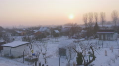 Panorama of a Village Small Houses Bare Branches Trees Sunset Pink Sky Snow is Stock Footage