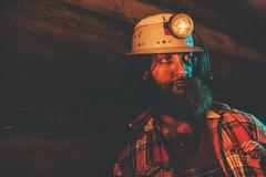 Miner Wearing Helmet Lamp and Leaning Against Wall Stock Photos