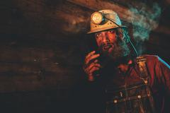Miner Wearing Helmet Lamp and Smoking Cigarette - stock photo