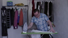 The man ironing a shirt Stock Footage