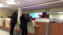 People at service counter talking to the teller inside CIBC Bank Stock Footage