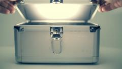A man open a metal suitcase and from the suitcase shine out  white beam of light Stock Footage