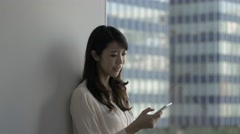 Attractive Japanese young woman with smartphone in a modern office Stock Footage