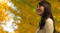 Attractive Japanese young woman in a city park in Autumn Stock Footage