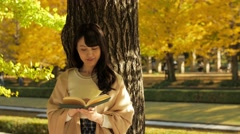 Attractive Japanese young woman reading a book in a city park in Autumn Stock Footage