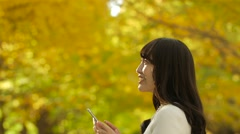 Attractive Japanese young woman with smartphone in a city park in Autumn Stock Footage