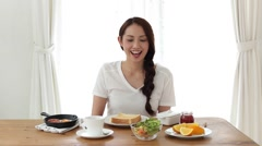 Attractive Japanese young woman eating breakfast at home Stock Footage