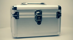 Metallic suitcase with chrome corners is rotates on a white background Stock Footage