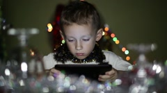Boy playing on the tablet in the New Year's Eve Stock Footage
