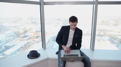 architect sits on a background of a large window with a laptop in his hand Stock Footage