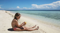 Young girl on the beach eating mango fruit Stock Footage