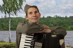 Portrait of Soviet soldier with accordion outdoors Stock Photos