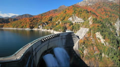 Autumn leaves and water discharge at Kurobe Dam in Toyama Prefecture Stock Footage