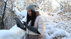 Beautiful happy woman typing on the tablet. Snow covered trees in winter park Stock Footage