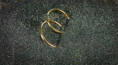 Close up rotation of golden wedding rings on the black sand. Stock Footage