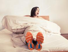 Wake up yawning girl in run shoes sitting in bed - stock photo