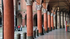 People walk by the arcade at Piazza Santo Stefano in Bologna, Italy. Stock Footage