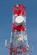 Multifunctional telecommunication tower - antennas on red and white pylon. Stock Photos