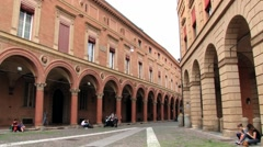 Pople walk by the arcade at Piazza Santo Stefano in Bologna, Italy. Stock Footage