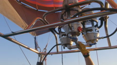 Pilot feeds flame to hot air balloon - stock footage