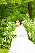 Beautiful bride with wedding bouquet of flowers outdoors in spring  park - stock photo