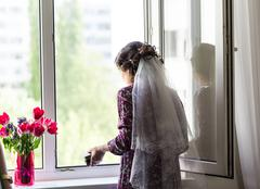 Beautiful young bride with wedding makeup and hairstyle in bedroom, newlywed Stock Photos