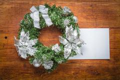 Green christmas wreath with card on wood - stock photo