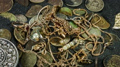 Treasure lots of pieces gold jewelry and coins close-up rotation on the sand. Stock Footage