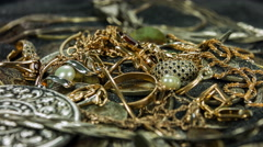 Old coins and gold treasures in a dark sand close-up rotation. - stock footage