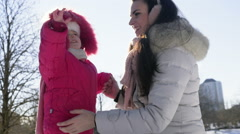 mother and daughter walking in the park on a sunny winter day - stock footage