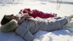 Stock Video Footage of mother and daughter chilling on the snow on a sunny winter day slow motion