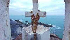 White cross with flowers on the hill at the ocean coast Stock Footage