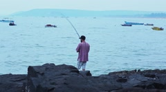 Fisher fisherman catches a fish on the ocean coast Stock Footage