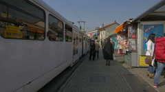 People walking by a tram stopped in the tram station, Sarajevo Stock Footage