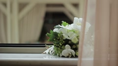 Elegant bridal bouquet  in light colors lying on the windowsill - stock footage