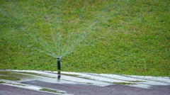 Jets of Water Spraying from a Rotating Sprinkler Head. UltraHD video Stock Footage