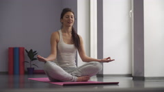 Yoga girl meditating and making a zen symbol with her hand. - stock footage