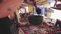 Customer tries out indian souvenir - sounding bowl Stock Footage