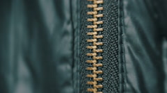 Stock Video Footage of Hand unzipped and fasten golden colored metallic zipper on dark clothes. Macro