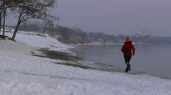 Girl runs along the bank of the Danube in winter. Stock Footage